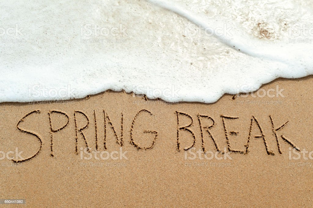 text spring break in the sand of a beach stock photo