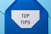 Text TOP TIPS on paper in blue envelope. Business concept