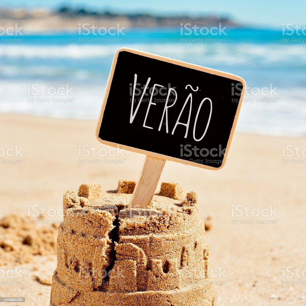 text verao, summer in Portuguese, in a sandcastle stock photo