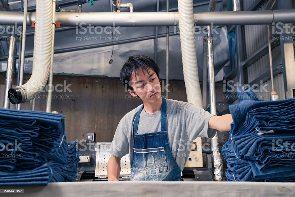 textile industry worker checking inventory with digital tablet before shipping stock photo