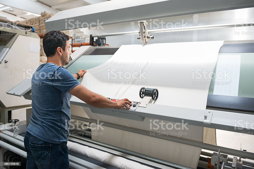 Textile quality controller checking fabrics stock photo