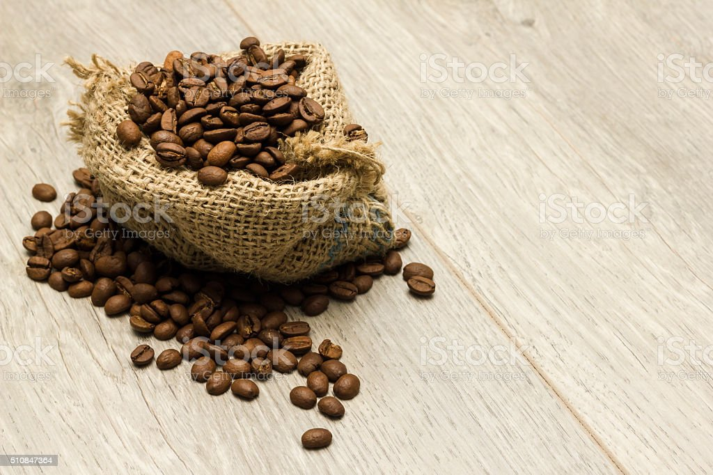 Textile sack full of roasted coffee beans on wooden table stock photo