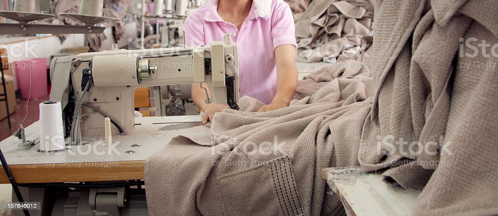 Textile worker is working on a sewing machine stock photo