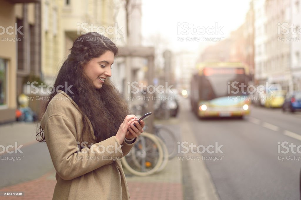 Texting brunette woman reads her phone and smiles stock photo