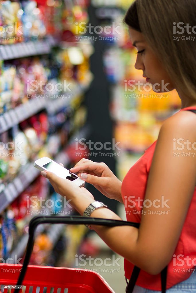 Texting in grocery store stock photo