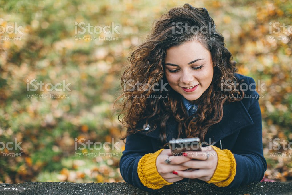 Texting in park stock photo