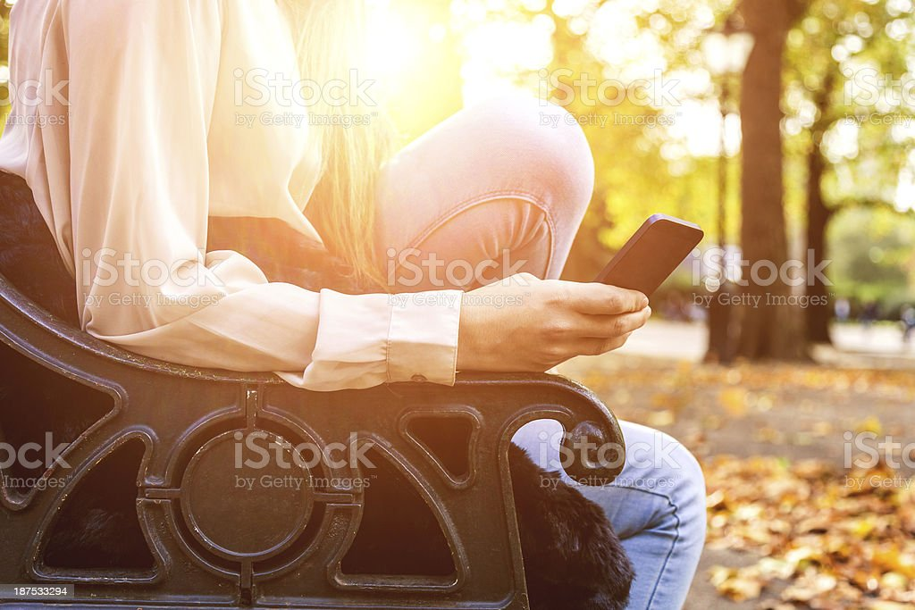 Texting in the park stock photo