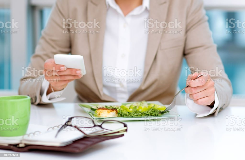 Texting messages and having lunch stock photo