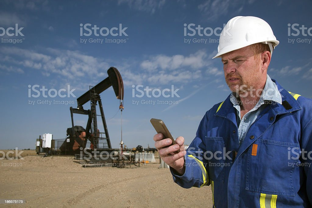 Texting Oil Worker royalty-free stock photo