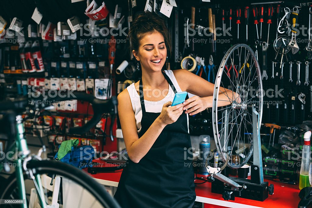 Texting on the phone while fixing a bicycle stock photo