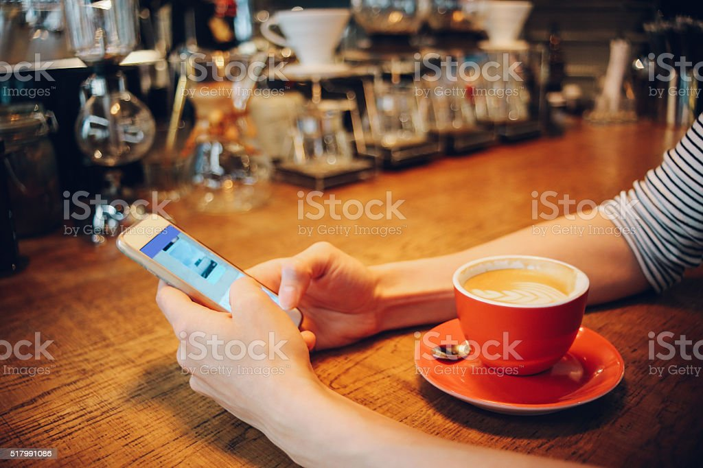 Texting on the smartphone on the coffee break stock photo