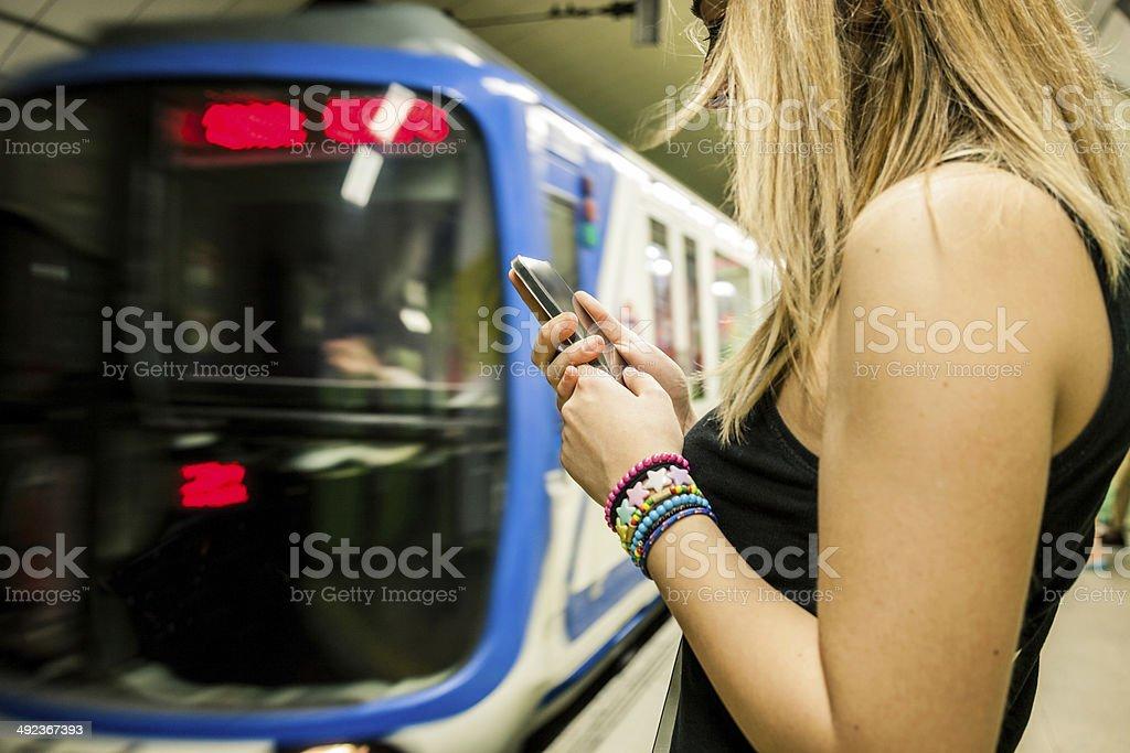 Texting on the subway platform royalty-free stock photo