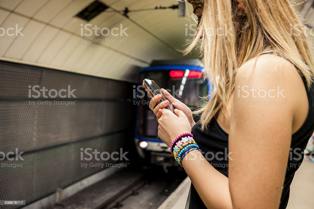 Texting on the subway platform stock photo