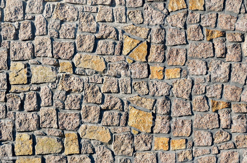 Texture of a wall built of granite stones stock photo