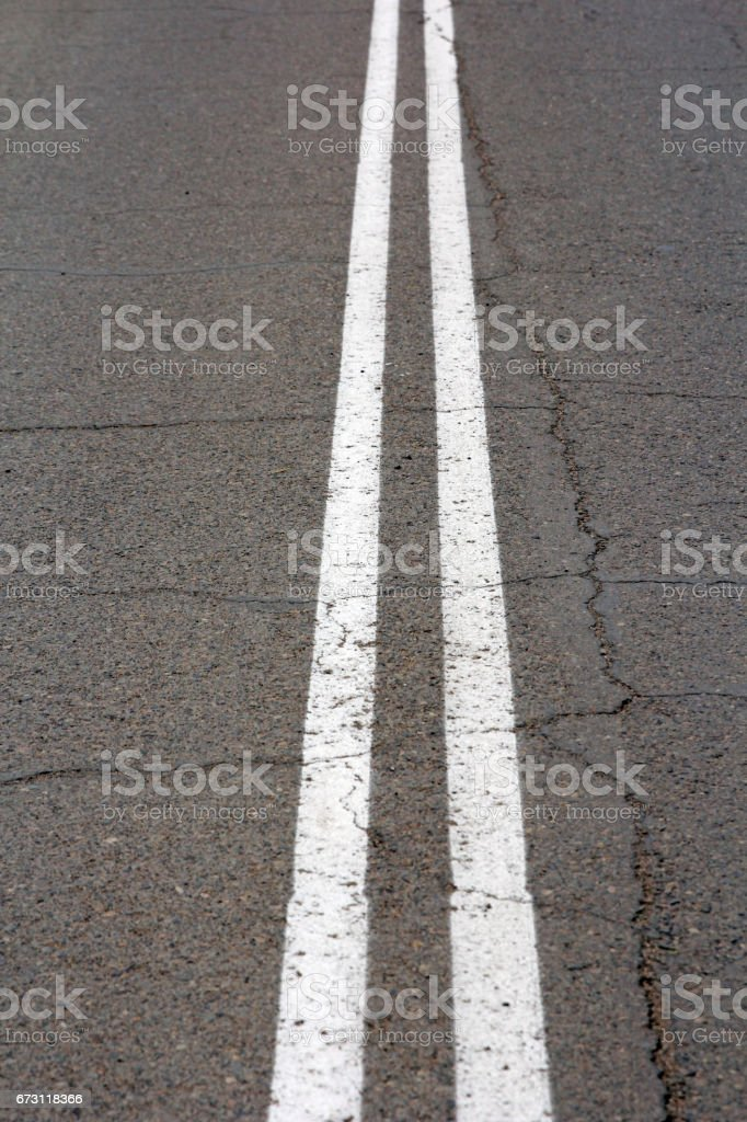 Texture of an asphalt road with a top view of a double white strip stock photo