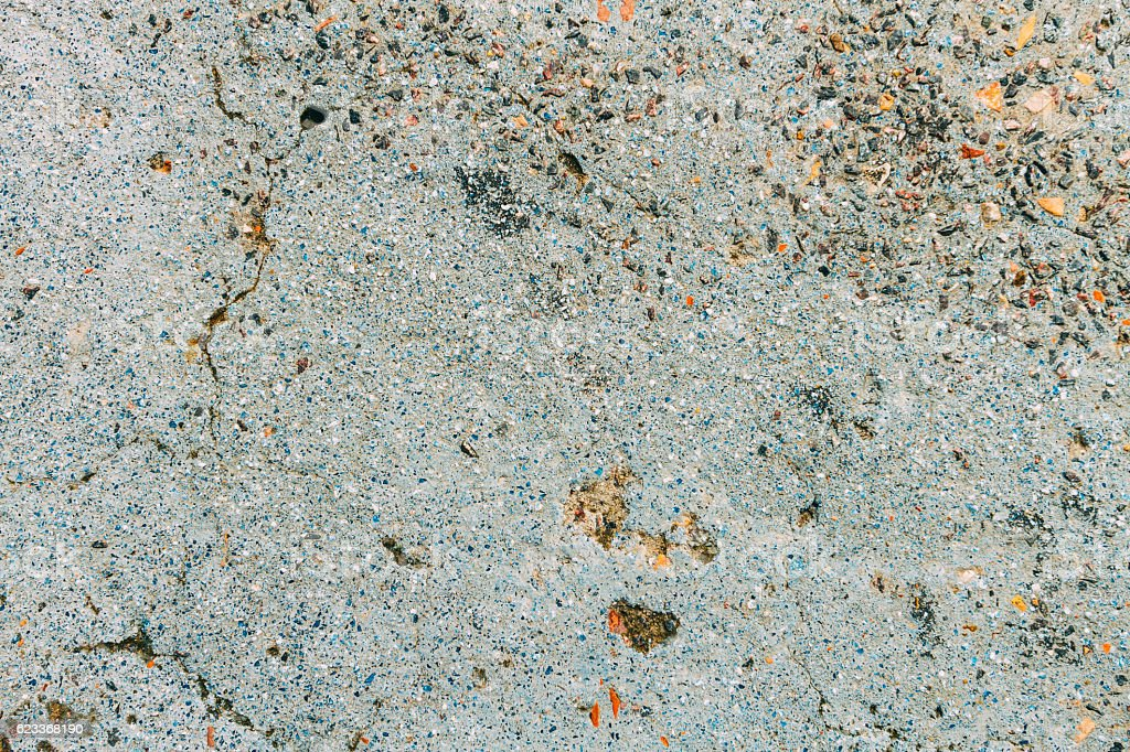 Texture of blue cement floor aged with small colored stones stock photo