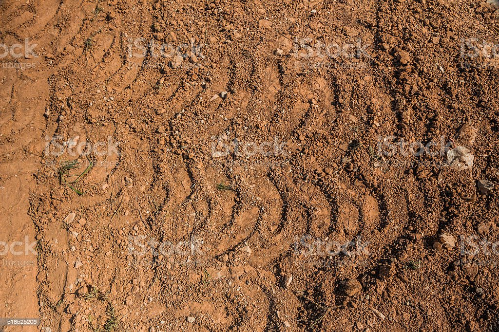 Texture of brown dirt with tractor tyre tracks stock photo