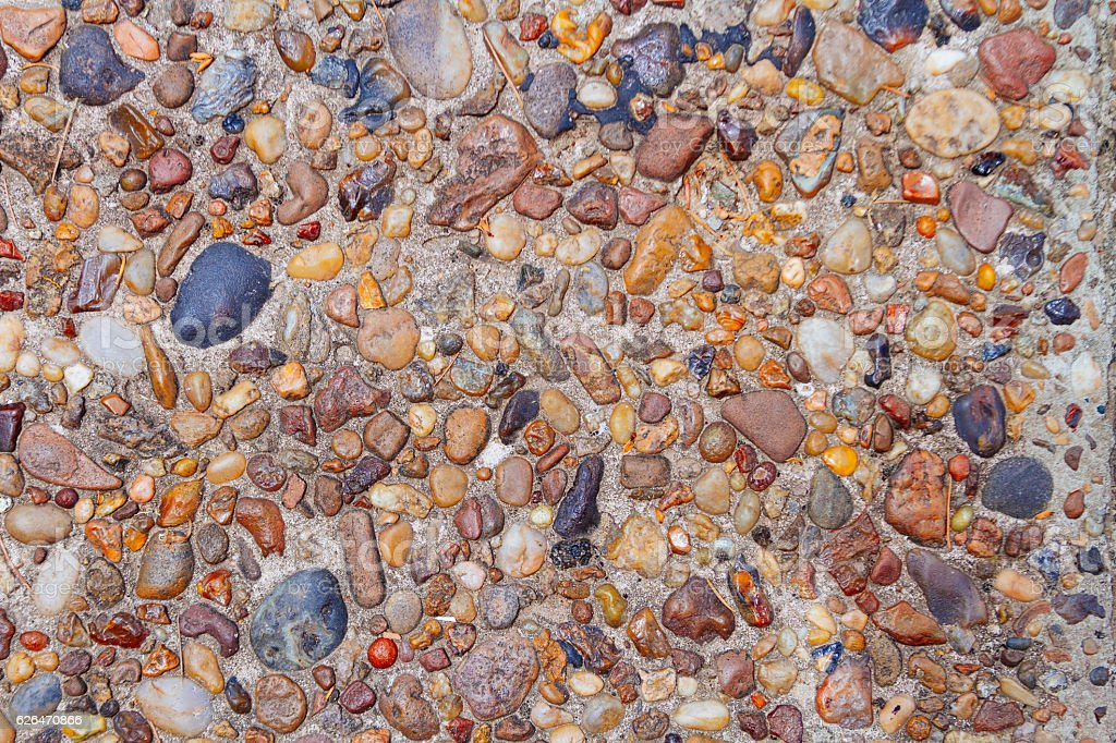 Texture of cement floor aged with small colored stones stock photo