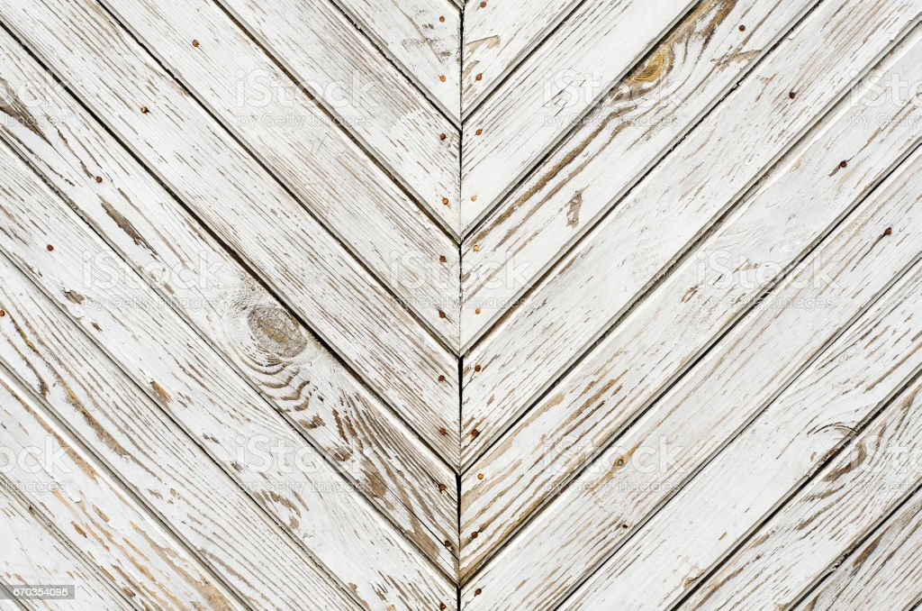 Texture of the old wooden gate which is covered with shabby white paint. Oblique lines mirrored stock photo