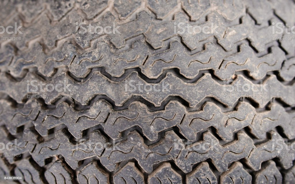 Texture of thick-skinned rubber tire colored in dark gray with carved pattern stock photo