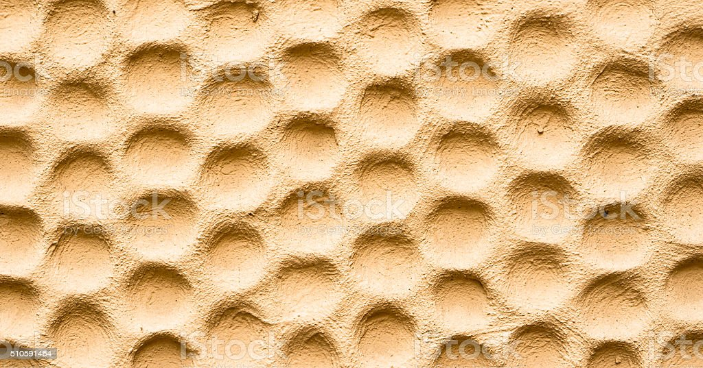 Texture of yellow wall plastered in form of honeycombs stock photo