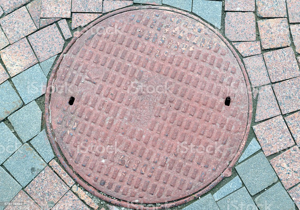 Textured metal manhole cover with holes, closing the technological well stock photo