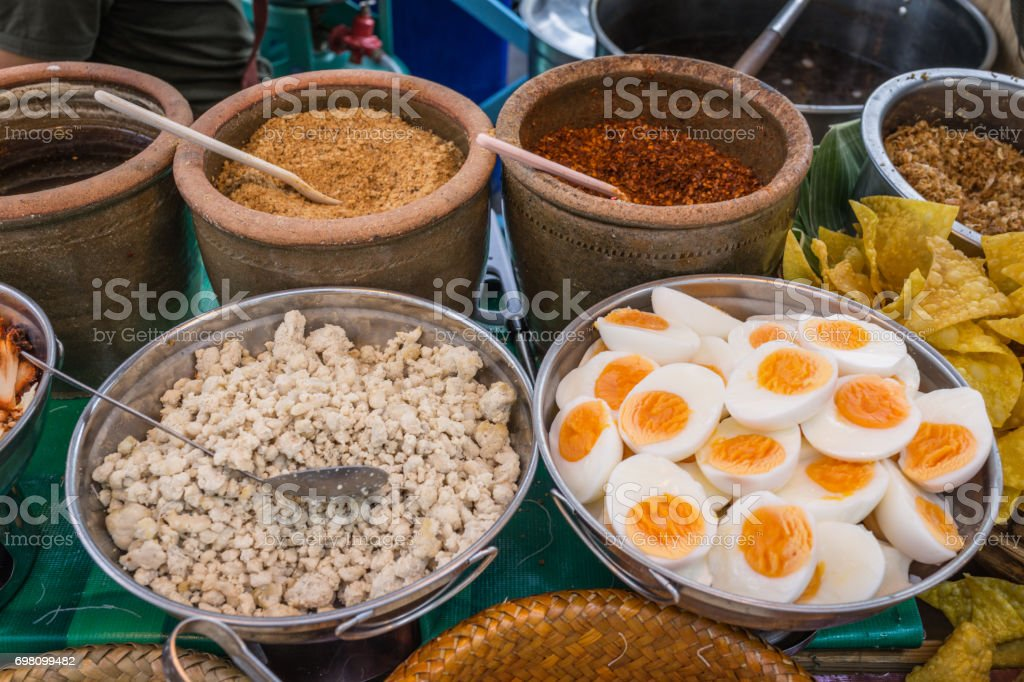 Thai and Asian noodle ingredient as pork, boiled egg, chili and peanut in street food market stock photo