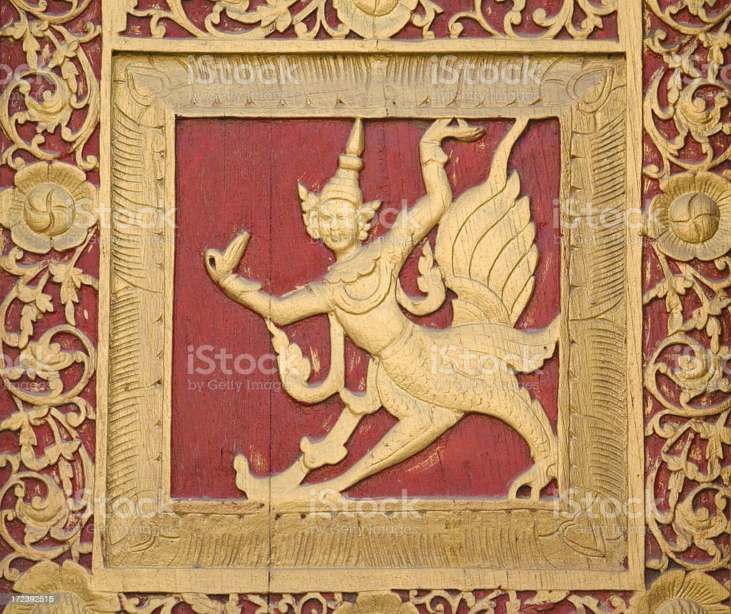 Thai Angel (apsara) in high-relief woodcarving stock photo