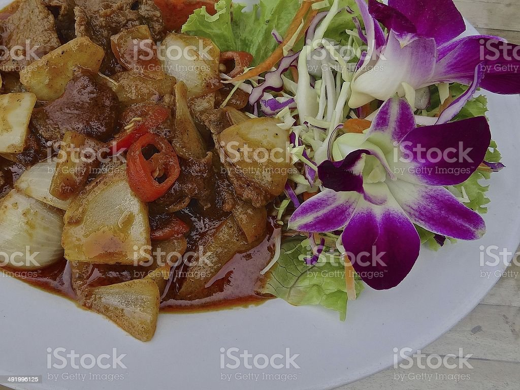 Thai beef red curry with flower garnish on a white royalty-free stock photo
