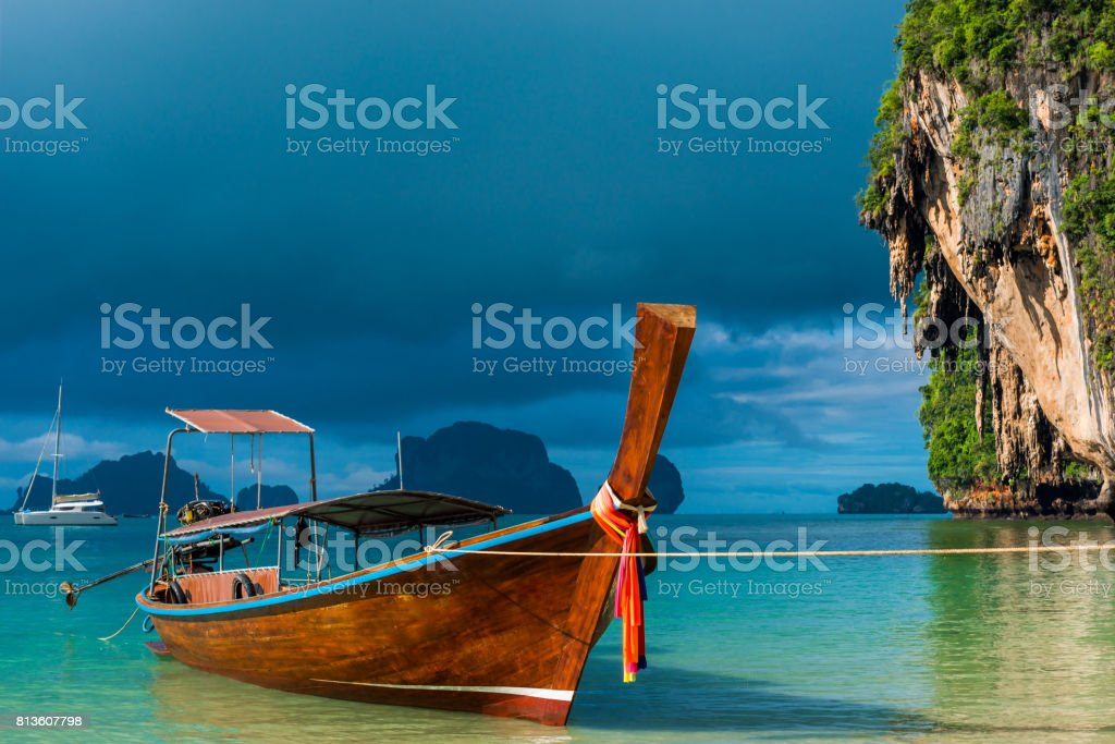 A Thai boat with a long tail near the shore, a blue rain cloud over the Andaman Sea stock photo