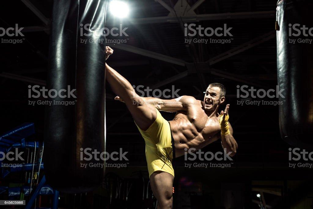 Thai boxer punch kick by punching bag stock photo