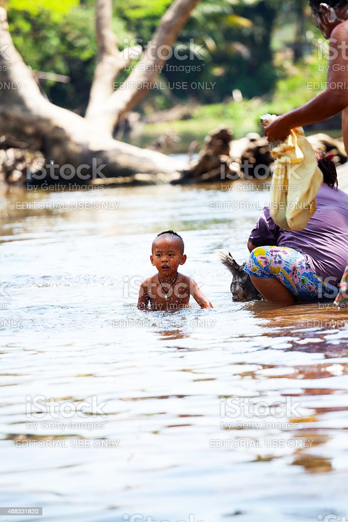 Thai boy sitting in river Phetchaburi stock photo