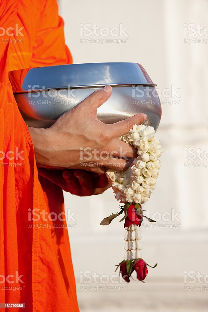 Thai Buddhist monk holding an alms bowl and flower garland. stock photo