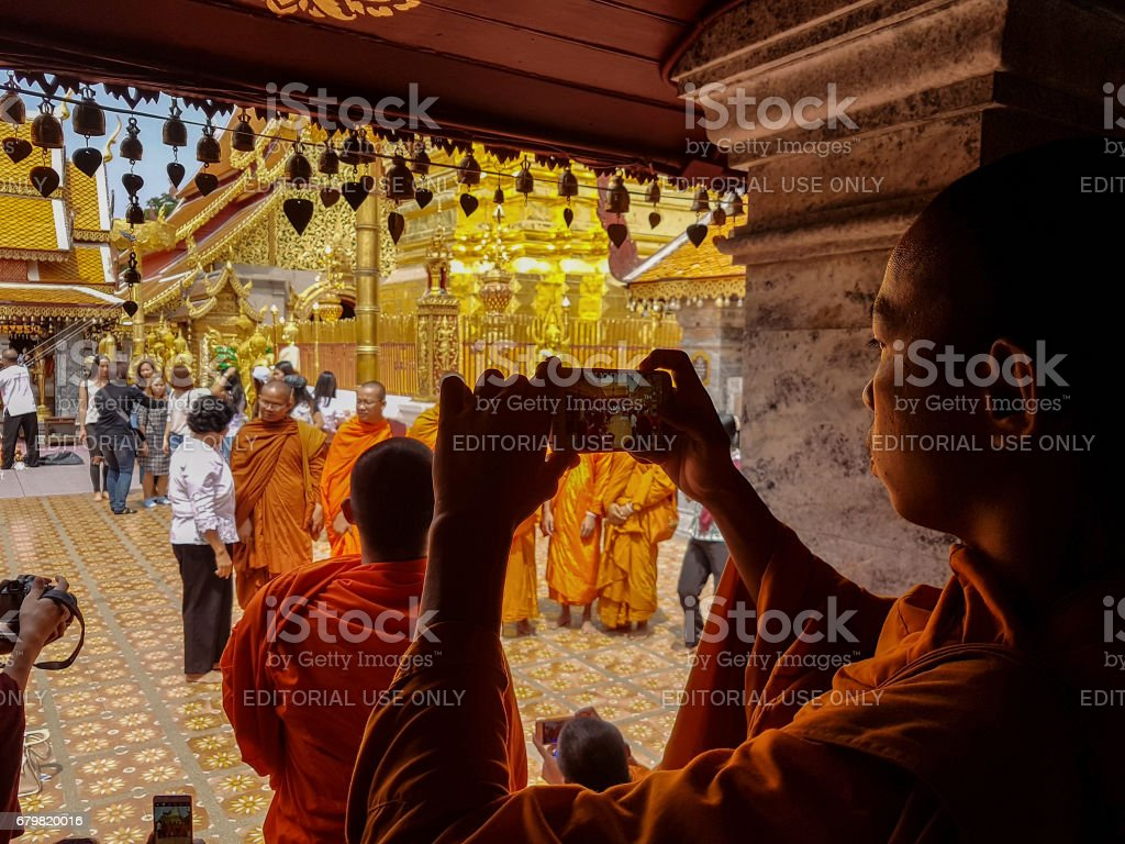 Thai Buddhist monk taking a photograph with a mobile phone of a group of monks at Wat Doi Suthep in Chiang Mai, Thailand. stock photo