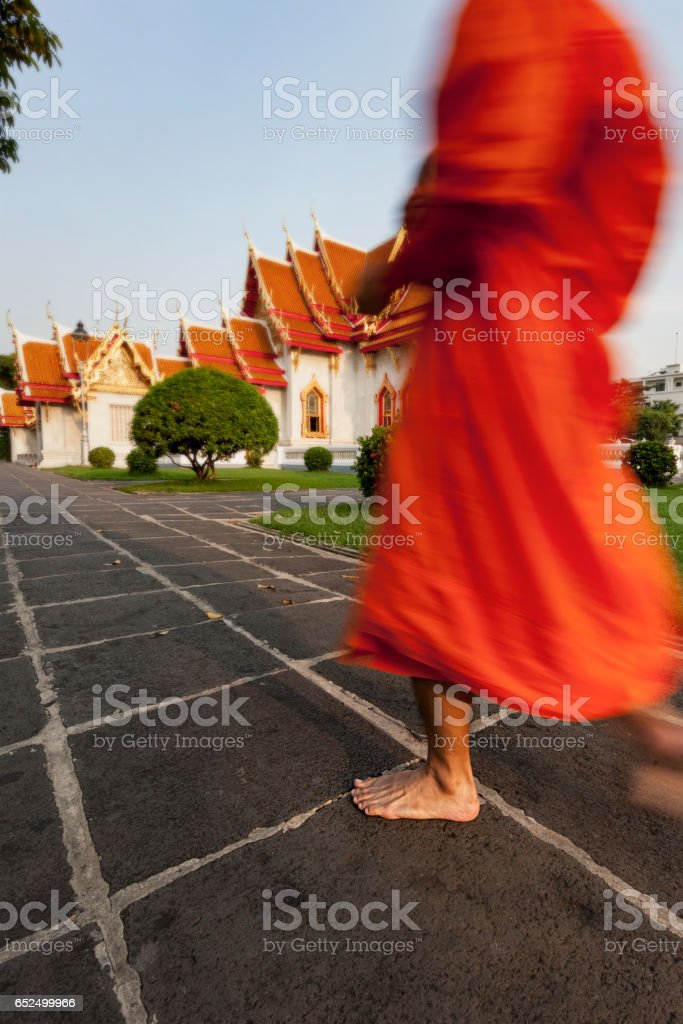Thai Buddhist monk walks barefoot in the grounds of the Thai Buddhist temple of Wat Benchamabophit in the early morning returning from having just collected alms. stock photo