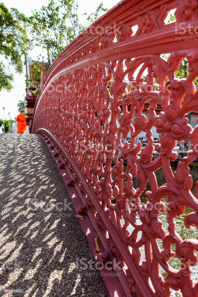 Thai Buddhist monk walks over a historic bridge in the grounds of the Thai Buddhist temple of Wat Benchamabophit in the early morning on his way to collect alms. stock photo