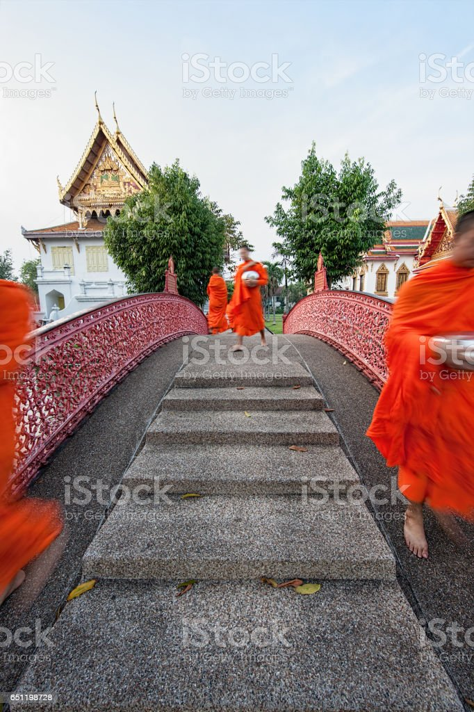 Thai Buddhist monks walk over a historic bridge in the grounds of the Thai Buddhist temple of Wat Benchamabophit in the early morning on their way to collect alms. stock photo
