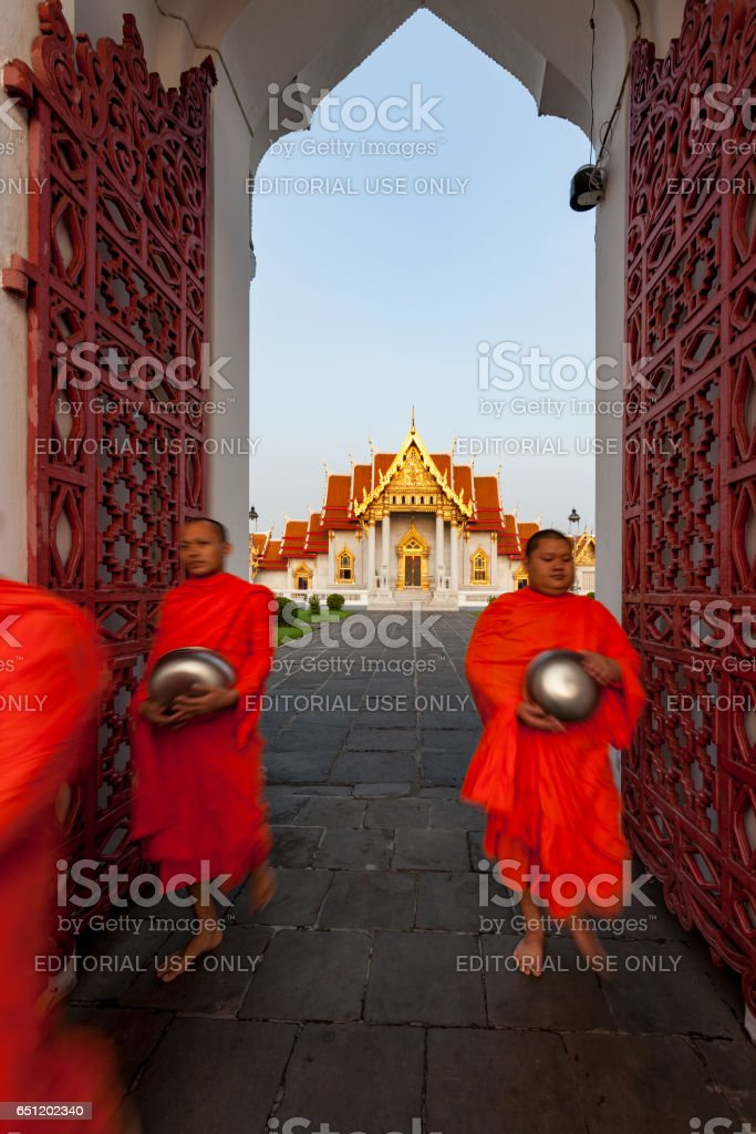 Thai Buddhist monks walk through the main iron gate of the Thai Buddhist temple of Wat Benchamabophit in the early morning on their way to collect alms. stock photo