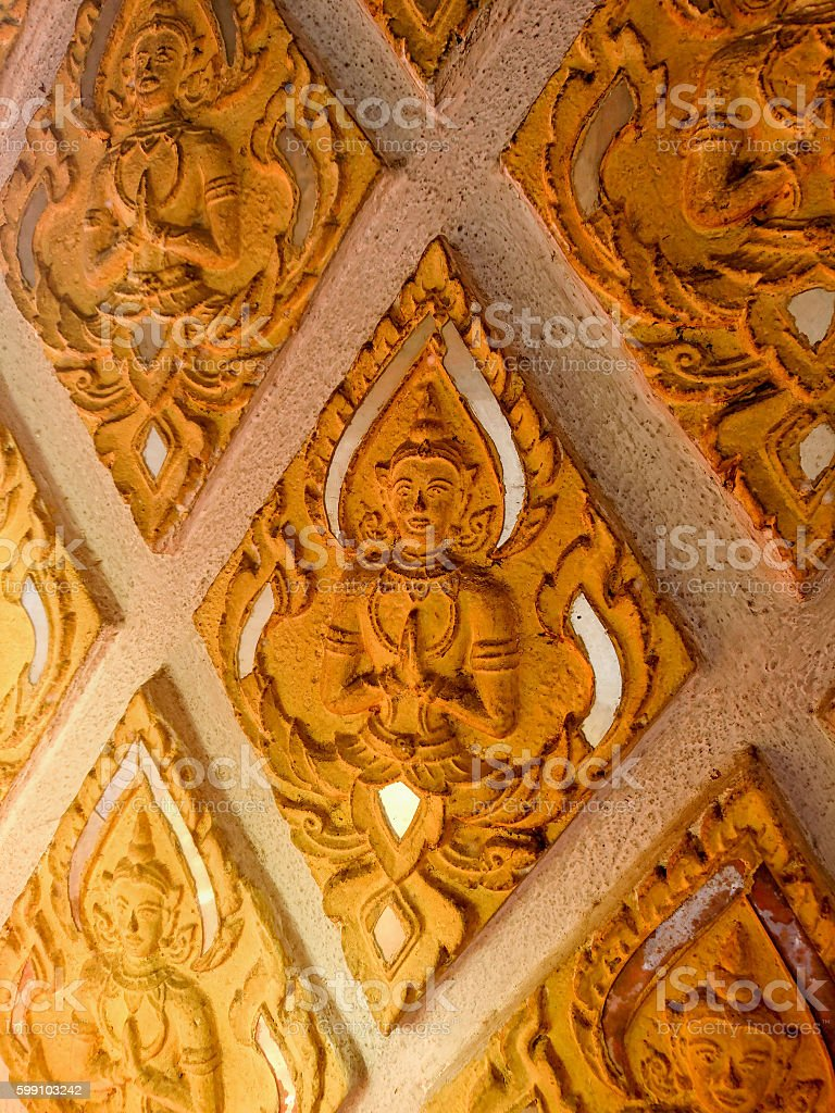 Thai Buddhist temple decoration of angels with floral motif. stock photo