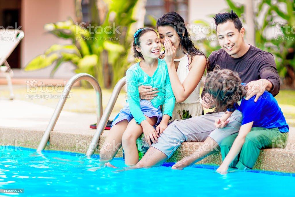 Thai family having fun playing near the swimmimg pool. Wet clothes stock photo