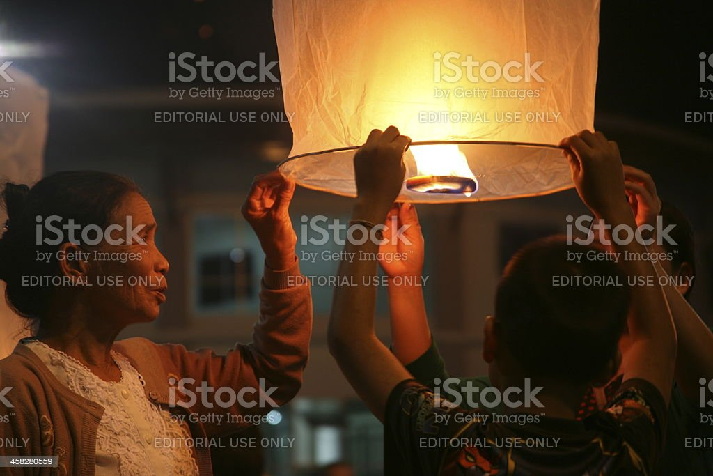 Thai family letting a lantern float into the air. royalty-free stock photo
