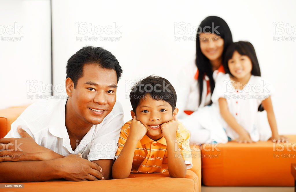 Thai family lying on the sofa in living room. royalty-free stock photo