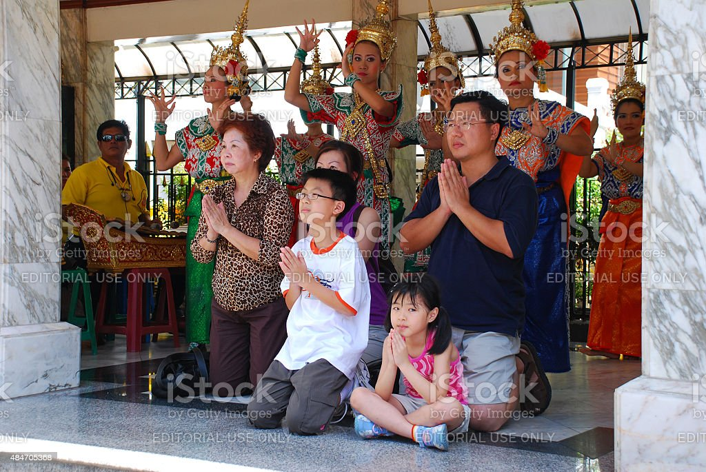 Thai family praying at Bangkok's Erawan Shrine stock photo