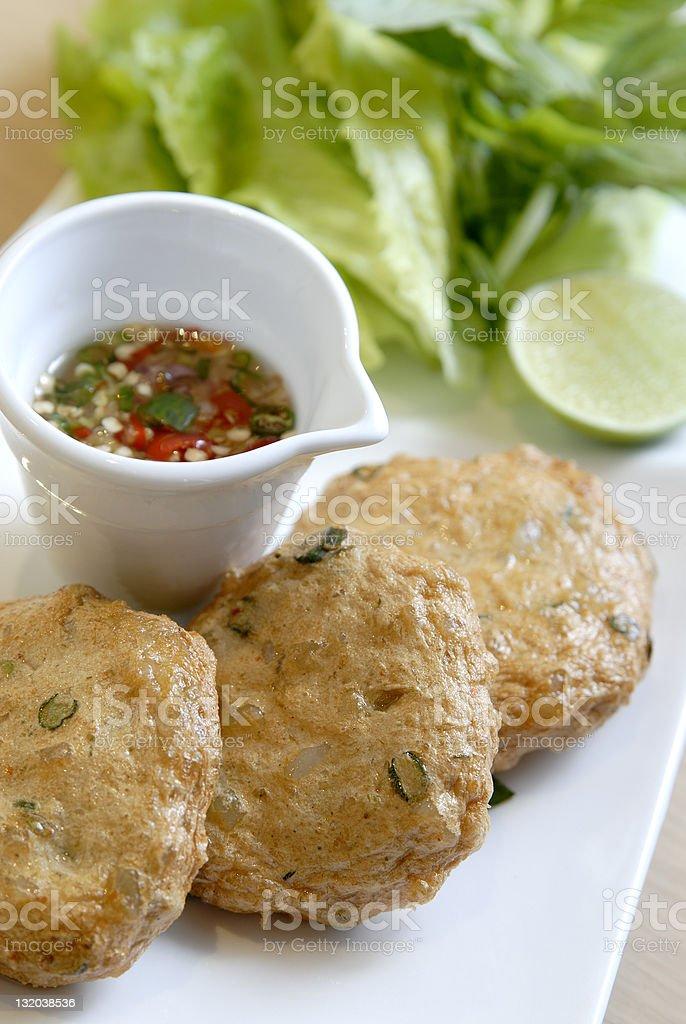 Thai fishcakes with oil sauce, lemon, lettuce on white plate royalty-free stock photo