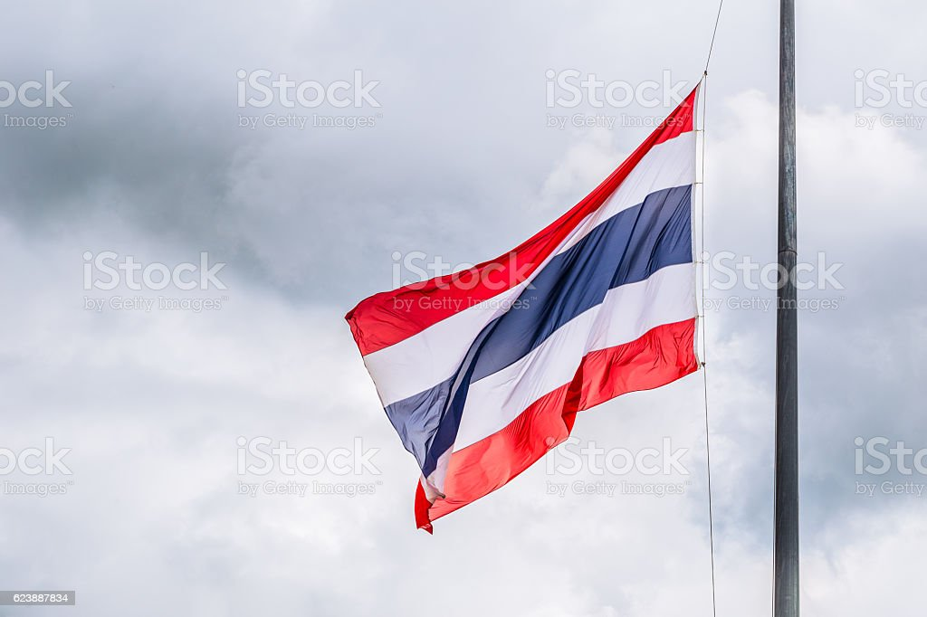 Thai flags half-mast on cloudy storm background. stock photo