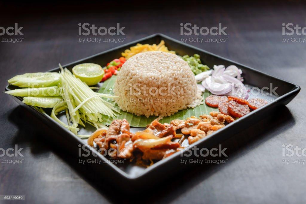 Thai food - Rice mixed with shrimp paste (Kao Cluk Ka Pi) with side dish as a mango, lemon, chili, cucumber, scrambled egg, cow-pea, shallots, Chinese sausage, dried shrimp and pork stock photo