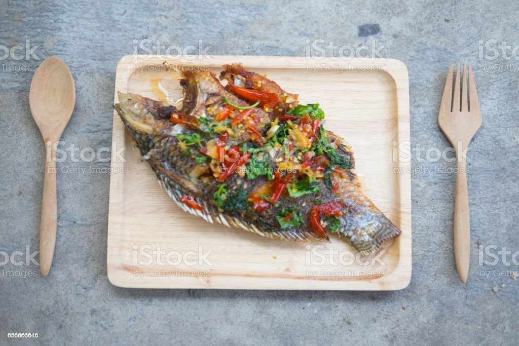 Thai fried Tilapia cuisine Spicy and sour herb on wooden tray stock photo