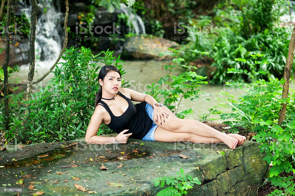 Thai girl fashion shot on rock at river stock photo