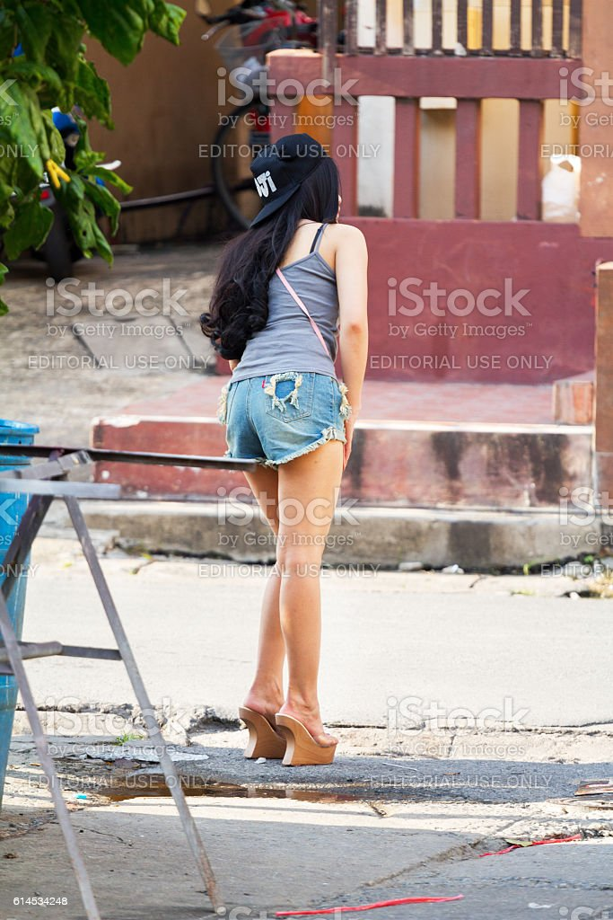 Thai girl in hot pants looking into street stock photo