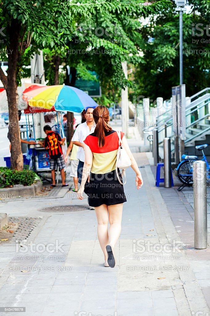 Thai girl on sidewalk near MRT station stock photo